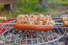 Ciérrese encima de parrilla de la barbacoa con la carne y las salchichas que cocinan durante su imagen de archivo