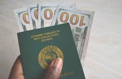 Ciérrese encima de pasaporte nigeriano con moneda de los dólares