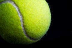 Ciérrese encima de pelota de tenis en blackground negro Fotos de archivo libres de regalías