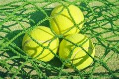 Ciérrese encima de pelotas de tenis en red fotografía de archivo libre de regalías