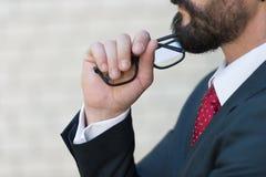 Ciérrese encima de perfil del hombre de negocios barbudo y dé sostiene los vidrios Hombre en traje azul y lazo rojo que piensa so fotografía de archivo