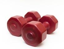 Ciérrese encima de pesas de gimnasia rojas aisladas de la aptitud Imagen de archivo libre de regalías