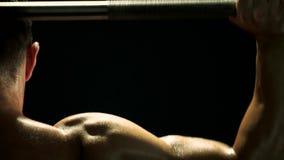 Ciérrese encima de pesos de elevación del hombre muscular sudoroso metrajes