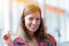 Ciérrese encima de plan de una empresaria sonriente en un centro de llamada fotografía de archivo