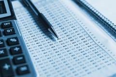 ciérrese encima de pluma con la calculadora en el informe de negocios, cuenta de las finanzas fotografía de archivo libre de regalías