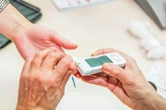 Ciérrese encima de proceso de la prueba móvil de la diabetes para el nivel del azúcar Nivel de azúcar de sangre normal El doctor  foto de archivo libre de regalías