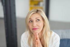 Ciérrese encima de señora adulta rubia pensativa Looking Up Imagen de archivo libre de regalías