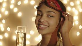 Ciérrese encima de tiro de la máscara del carnaval de la mujer que lleva negra con el vidrio del champán en su mano almacen de metraje de vídeo