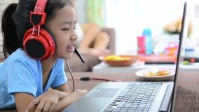 Ciérrese encima de tiro de la niña asiática que usa el ordenador portátil y el auricular en casa almacen de metraje de vídeo