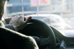 Ciérrese encima de tiro de las manos del ` un s del hombre que sostienen un volante del ` s del coche Conducción de seguridad en  Imagen de archivo libre de regalías