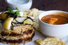 Ciérrese encima de tiro de un plato indio del arroz del biryani del huevo con salsa y el adorno Foto de archivo libre de regalías