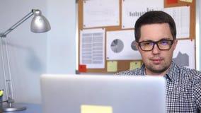 Ciérrese encima de tiro de una cara del ` s del hombre que trabajando con el ordenador portátil en la oficina metrajes