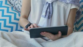 Ciérrese encima de tiro de una mujer joven que hace negocio en una tableta en casa en el sofá metrajes
