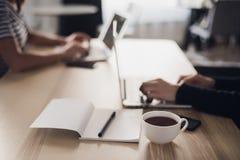 Ciérrese encima de tiro de una taza de café, de cuaderno con el lápiz o la pluma y de manos que mecanografían en el teclado de un foto de archivo