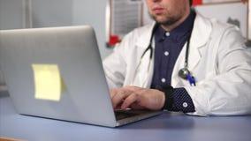 Ciérrese encima de tiro del médico de sexo masculino moderno en la capa blanca usando el ordenador portátil almacen de video