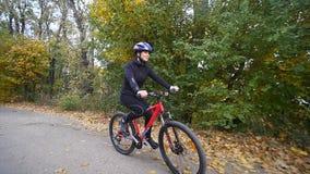 Ciérrese encima de tiro de la mujer joven en una bicicleta en el parque del otoño Cámara lenta almacen de metraje de vídeo