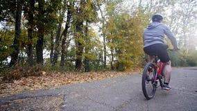 Ciérrese encima de tiro de la mujer joven en una bicicleta en el parque del otoño Cámara lenta almacen de video