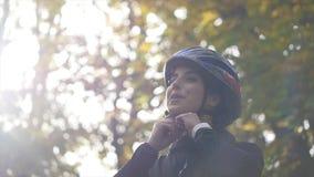 Ciérrese encima de tiro de la mujer joven en una bicicleta en el parque del otoño Cámara lenta Fondo de la luz del sol almacen de metraje de vídeo