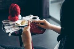 Ciérrese encima de tiro de las manos de la mujer joven que hacen punto un handicra rojo de la bufanda Foto de archivo libre de regalías