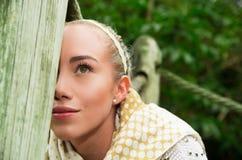 Ciérrese encima de tiro si muchacha rubia joven que se sienta en un puente de madera que camina Imágenes de archivo libres de regalías
