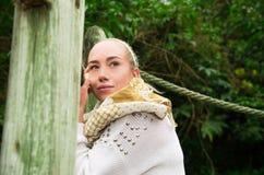 Ciérrese encima de tiro si muchacha rubia joven que se sienta en un puente de madera que camina Imagen de archivo