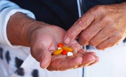 Ciérrese encima de tiro de una mano que lleva a cabo varias medicinas Foto de archivo libre de regalías