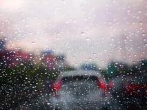 Ciérrese encima de una gota del agua de la lluvia en un winshield con el atasco borroso en una calle, foco selectivo, textura del Imagen de archivo