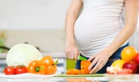 Ciérrese encima de verduras de los cortes de la mujer embarazada Foto de archivo libre de regalías