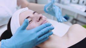 Ciérrese encima de vista de la cara femenina hermosa que tiene masaje plástico del cosmetólogo Atención sanitaria, cuidado de pie almacen de metraje de vídeo