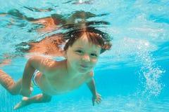 Ciérrese encima de vista de la pequeña natación del muchacho debajo del agua Fotografía de archivo