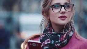 Ciérrese encima de vista de un mensaje que manda un SMS de la chica joven atractiva en el centro de ciudad Belleza natural, maqui metrajes