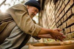 Ciérrese encima de vista de la mano que se lava del hombre sin hogar en la calle Foto de archivo