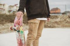 Ciérrese encima del adolescente que se coloca en una sudadera con capucha del lado derecho que sostiene un monopatín de la mano e Fotos de archivo libres de regalías