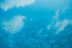 Ciérrese encima del agua azul en las nubes blancas de la reflexión de la piscina y del cielo azul Imagen de archivo