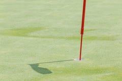 Ciérrese encima del agujero del golf con la asta de bandera en la hierba verde y su sombra i Fotografía de archivo