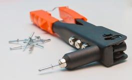 Ciérrese encima del arma de remache y haga estallar los remaches Foto de archivo libre de regalías