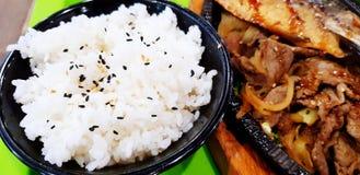 Ciérrese encima del arroz blanco en cuenco negro, los pescados de Saba, la carne y la cebolla frita con la salsa del teriyaki fotografía de archivo libre de regalías