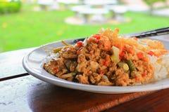 Ciérrese encima del arroz rematado con la comida picante de Tailandia de la albahaca del pollo en el escritorio de madera imagen de archivo libre de regalías