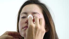 Ciérrese encima del artista de maquillaje que limpia la cara del ` s de la mujer almacen de metraje de vídeo