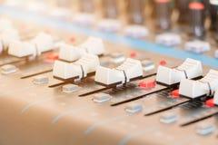 Ciérrese encima del atenuador volumen del mezclador de sonidos del viejo que ajusta el regulador de los botones en sala de contro fotos de archivo