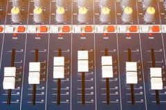 Ciérrese encima del atenuador volumen del mezclador de sonidos del viejo que ajusta el regulador de los botones en sala de contro imagenes de archivo