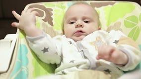 Ciérrese encima del bebé que sacude las piernas en la mecedora del cuarto de niños metrajes