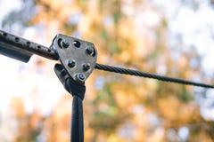 Ciérrese encima del cable de la seguridad, subiendo el engranaje en un parque de la aventura se enganchan a la escalada o pasar o fotografía de archivo libre de regalías