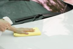 Ciérrese encima del coche de la limpieza de la mano de la mujer por el paño micro de la fibra Imagen de archivo
