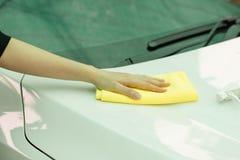 Ciérrese encima del coche de la limpieza de la mano de la mujer por el paño micro de la fibra Fotos de archivo libres de regalías