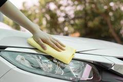 Ciérrese encima del coche de la limpieza de la mano de la mujer por el paño micro de la fibra Foto de archivo libre de regalías