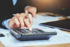 ciérrese encima del contable de la mano que usa la calculadora con el ordenador portátil concepto s imagenes de archivo