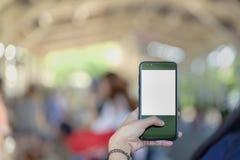 Ciérrese encima del control de la mano usando el teléfono elegante del fondo al aire libre de la calle del parque Fotos de archivo