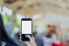 Ciérrese encima del control de la mano usando el teléfono elegante del fondo al aire libre de la calle del parque Imagen de archivo libre de regalías