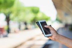 Ciérrese encima del control de la mano usando el teléfono elegante del fondo al aire libre de la calle del parque Fotografía de archivo